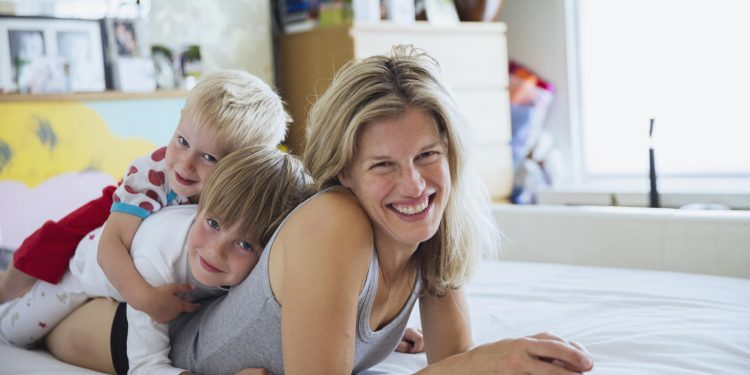 Portrait of mother with sons in bed lying one on top of another