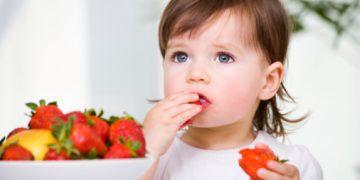 a little girl eating strawberries