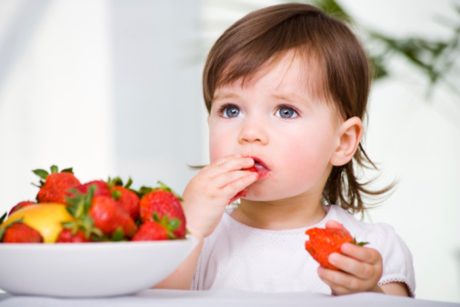 a little girl eating strawberries