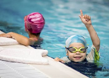 Children on swimming class on pool edge